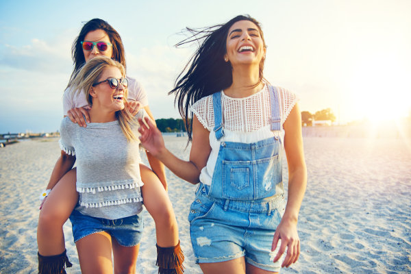 Three beautiful female friends having fun while carrying each other on beach at sunset
